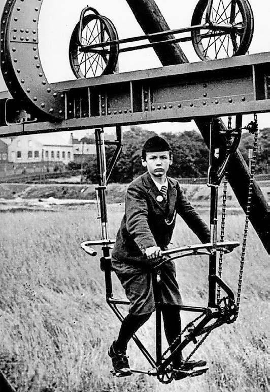 """So sahen die ersten Versuche von Schwebahn-Erfinder Eugen Langen aus: Per Schwebe-Fahrrad demonstrierte er 1895 auf einer Teststrecke in Köln-Deutz seine Idee eines schwebenden Gefährts. Die Industriellen aus dem engen Wupper-Tal waren begeistert. Foto: aufgenommen um 1895 von einem unbekannten Fotografen, aus dem Buch """"Wuppertal und die Schwebebahn"""" von Michael Malicke, Rheinisch-Westfälisches Wirtschaftsarchiv."""