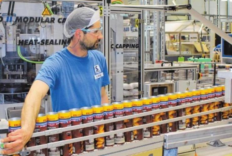 Maschinenführer Artur Michalka bedient die Wickelanlage für Snack-Dosen. An der Hochleistungslinie werden unter anderem Verpackungen für Erdnüsse, Kekse, vor allem aber für Stapelchips hergestellt.