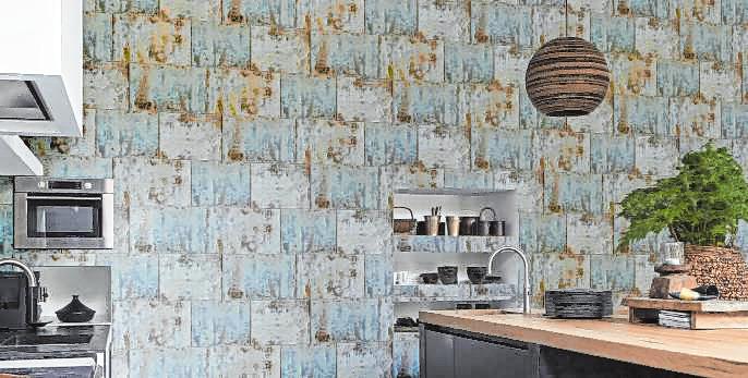 Mit Patina: Rasch gestaltet eine Küchenwand mit einer Tapete im Industrie-Look in zarten Blautönen.
