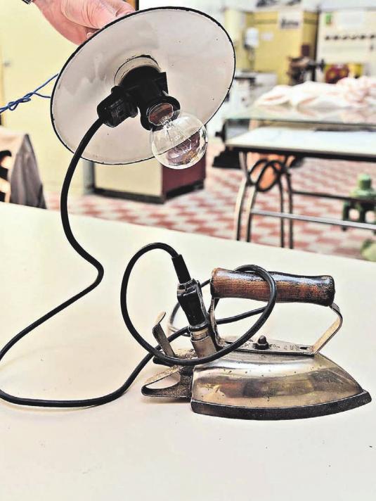 Die Anfänge der Stromnutzung: An der Deckenlampe befand sich eine Steckdose, in die die Hausfrau ihr Bügeleisen einstecken konnte. Der Vorteil: Bügeln mit gleichmäßiger Wärme und ohne Kohlenstaub.