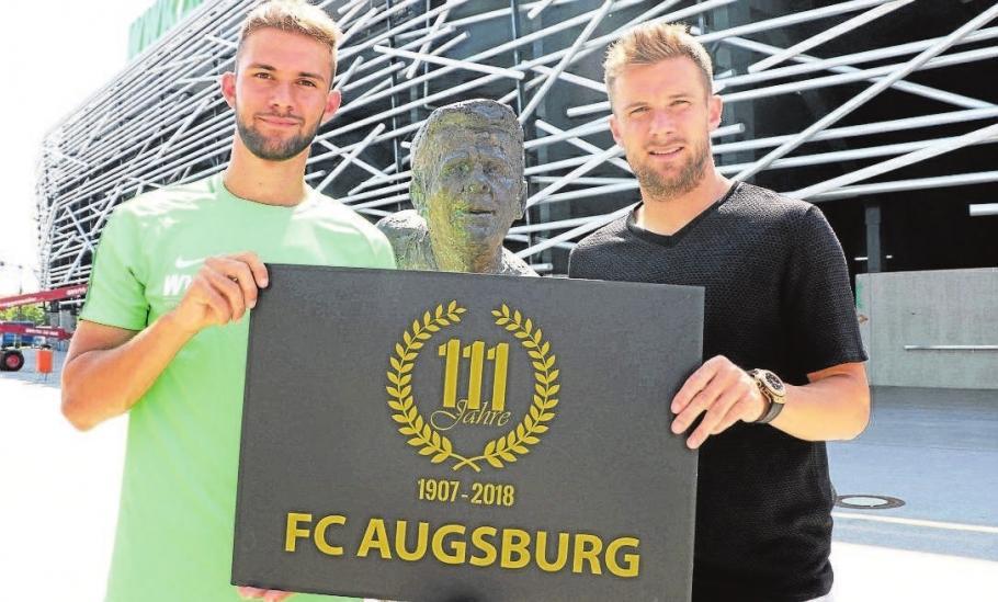 FCA-Nachwuchstalent Simon Asta (links) und Kapitän Daniel Baier freuen sich auf noch viele Aktionen und Feierlichkeiten rund um das 111-jährige Jubiläum des FC Augsburg. Hier präsentieren sie das eigens entworfene Jubiläums-Logo des Vereins. Foto: FC Augsburg