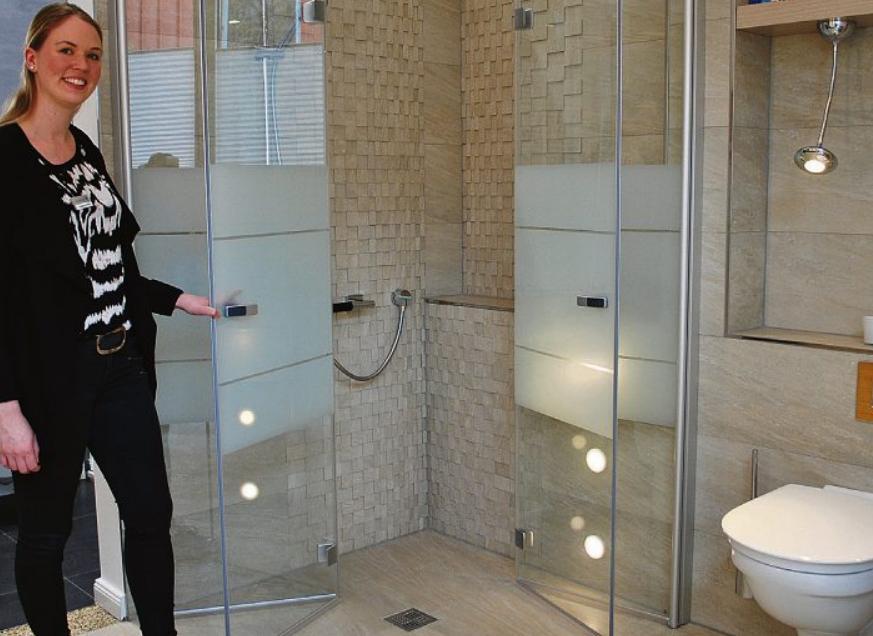 Barrierefreie Bäder mit bodenebener Dusche sind Trend: Ausstellungsberaterin Katharina Möller zeigt eine Version mit Falt-Pendel-Tür.