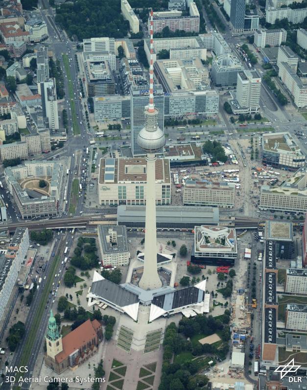 Blick aus der Höhe auf Mitte:In den Straßen und auf Plätzen rund um den Fernsehturm sind viele Pkw, Lkw und Busse gut zu erkennen