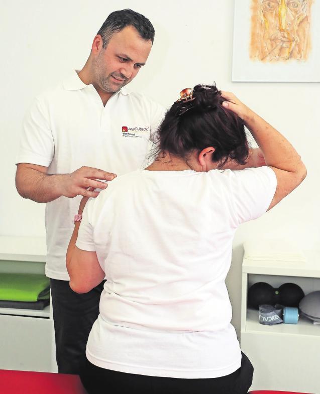 Wasi Behzad zeigt Patienten mit akuten Schmerzen in einem Workshop besondere Dehnübungen. Foto: André Kempner