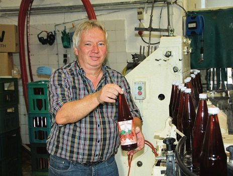 Martin Schmidt füllt roten Johannisbeer-Nektar in Flaschen ab +Foto: cs