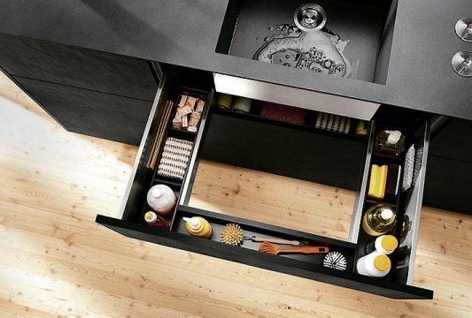 So lässt sich jeder Zentimeter im Spülenunterschrank komfortabel nutzen: mit einem U-förmigen Auszug unter dem Spülbecken, der Platz für diverse Putzutensilien bietet. Bild: AMK