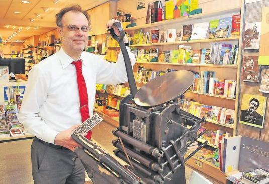 Die Kunden wollen nicht mehr nur den guten Rat des Verkäufers, sagt Buchhändler Michael Kozinowski, sondern auch ein Einkaufserlebnis mit allen Sinnen. Deshalb präsentierte er etwa beim Welttag des Buches eine alte Tiegeldruckmaschine. Archiv-Foto: Mathias Kehren