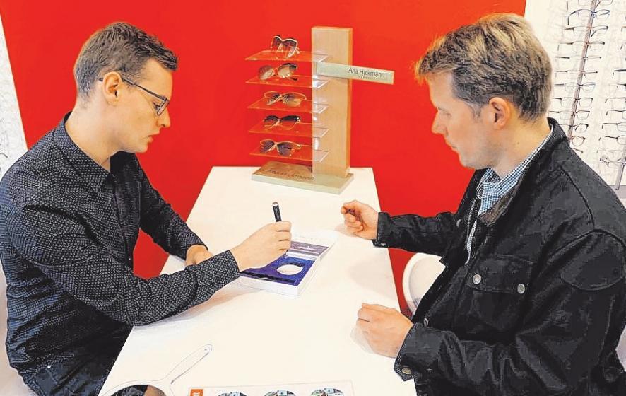 Augenoptiker André Mahlke zeigt einem Kunden die Wirksamkeit des Blaulicht-Filters unter LED-Beleuchtung. FOTO: HFR