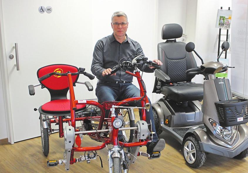 Geschäftsführer Ralf Hartz mit einer Auswahl möglicher Fahrzeuge – vom Dreirad bis zum Elektromobil. Foto: as