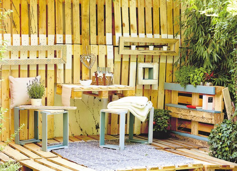 Alles paletti. Gemütliche Gartenecke zum Selberbauen: Eine Wand aus Paletten dient hier als Sichtschutz.Foto: frechverlag/dpa-mag
