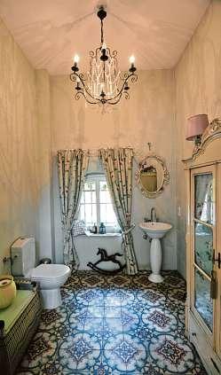 Das Bad mit Kronleuchter, Gardinen und historischen Fliesen.