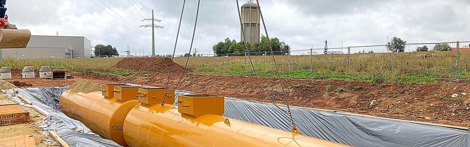 In der unterirdischen Tankanlage haben insgesamt 120 000 Liter Treibstoff Platz. Das Bild zeigt den Einbau der Tanks, im Hintergrund der Wasserturm an der Lüften.