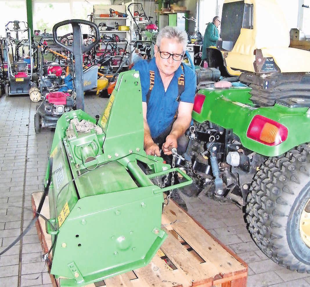 Werkstattmeister Christian Pursche passt eine Bodenfräse an einen Trecker an.