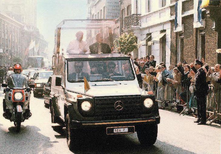 """Papst Johannes Paul II. in seinem Papstwagen Mercedes-Benz 230 G mit dem Kennzeichen SCV 7. Das Fahrzeug wird 1980 von Mercedes-Benz für den Vatikan gebaut, später folgt ein zweites """"Papamobil"""" auf Basis der G-Klasse"""