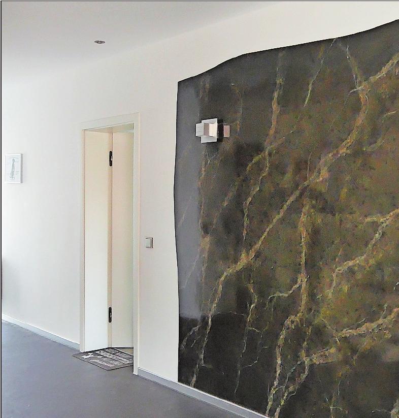 Sieht aus wie Marmor, ist aber eine in mehreren Arbeitsgängen gestaltete Wand: Malermeister Mario Becker hat dafür unter anderem Spachtelmasse verwendet. FOTO: BRÄUNLING