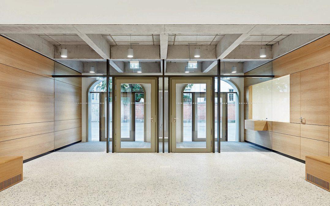 Die Kubatur des Baus respektierend, wird der Windfang als Holz-Glas-Konstruktion ins Innere gezogen. Das großzügige Foyer ist von unprätentiöser und doch würdiger Gestaltung, das Selbstverständnis der Institution Amtsgericht zum Ausdruck bringend. Fotografie: Dietmar Strauß, Besigheim