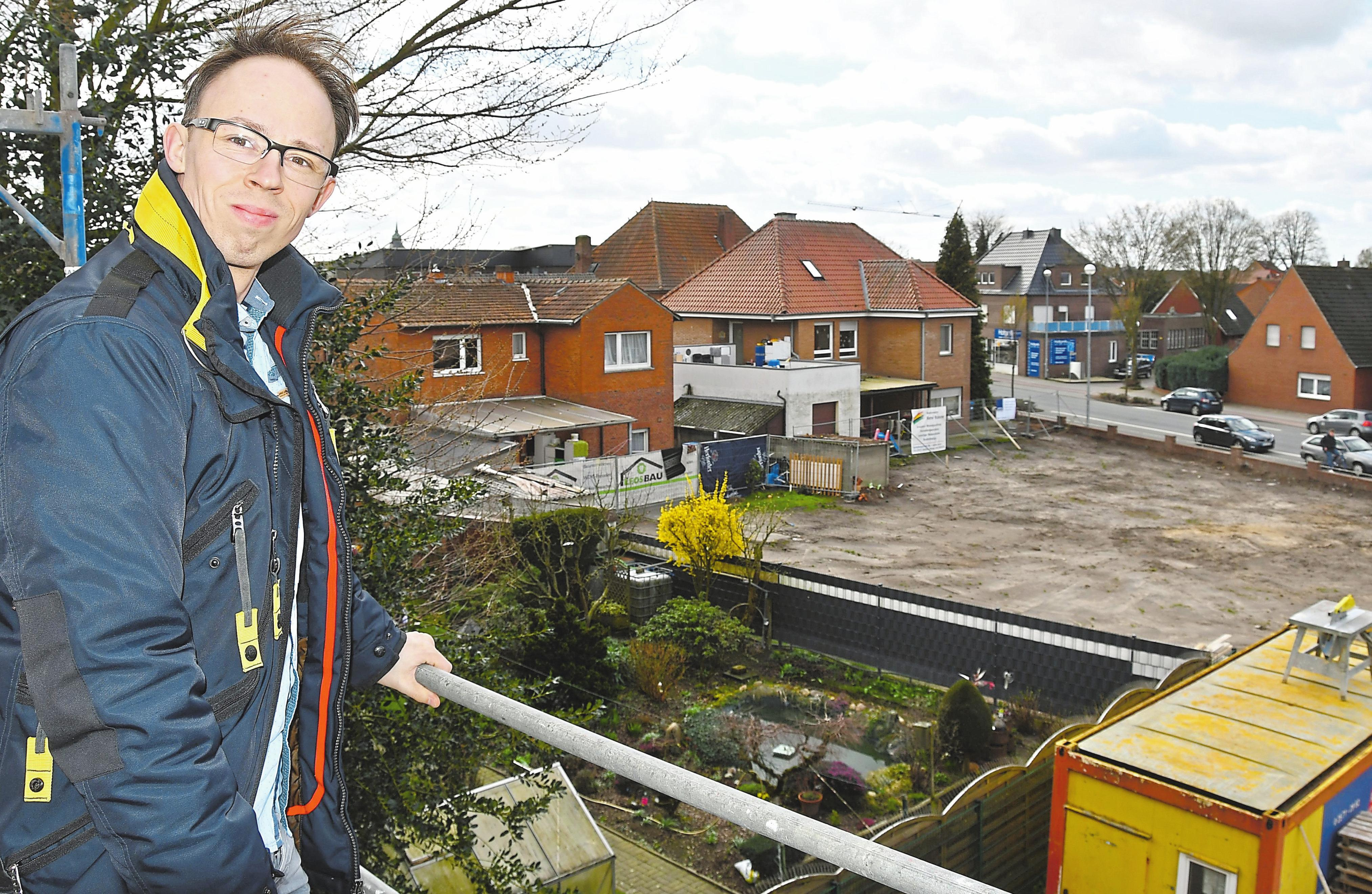 Tobias Ahaus vor der Fläche zur Saerbecker Straße, auf der eine dreigeschossige Riegelbebauung mit Staffelgeschoss und Laubengang gebaut wird.