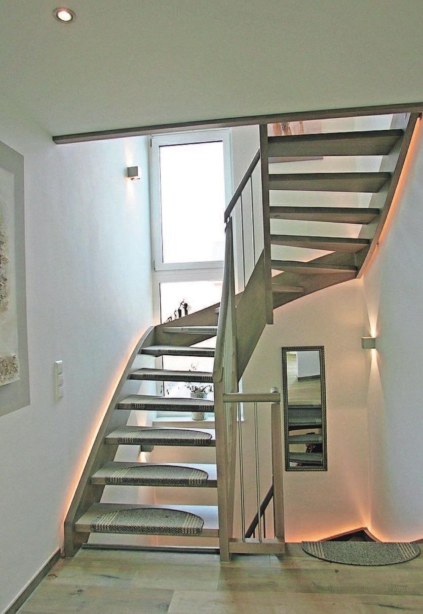 Ein Blickfang ist die Treppe ins OG mit LED-Beleuchtung und Edelstahlgeländer.