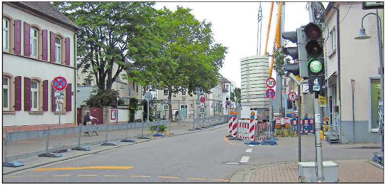Werden fürs Straßenfest abgebaut: die Behelfsampel und die Schutzbarken links vor dem protestantischen Pfarrhaus. FOTO: SCHAAR