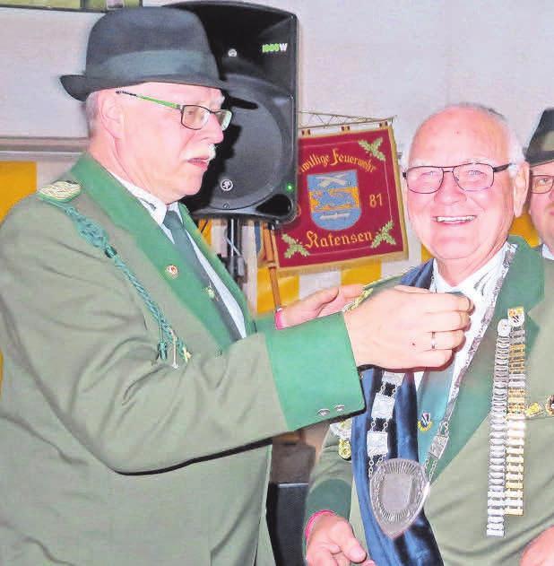 Der Vorsitzender Detlef Reinecke (links) legt Schützenkönig Otto Brandes die Kette an.