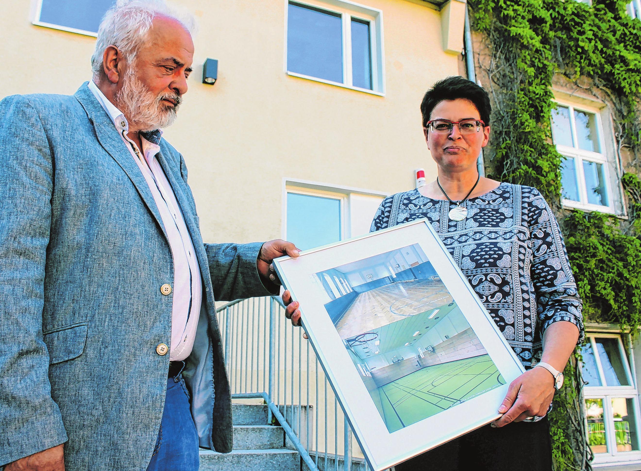Bürgermeister Ronald Seeger überreichte Schulleiterin Kerstin Pollak eine Vorher-Nachher-Aufnahme zur Erinnerung an die Sanierung der Turnhalle. Foto: Bohm