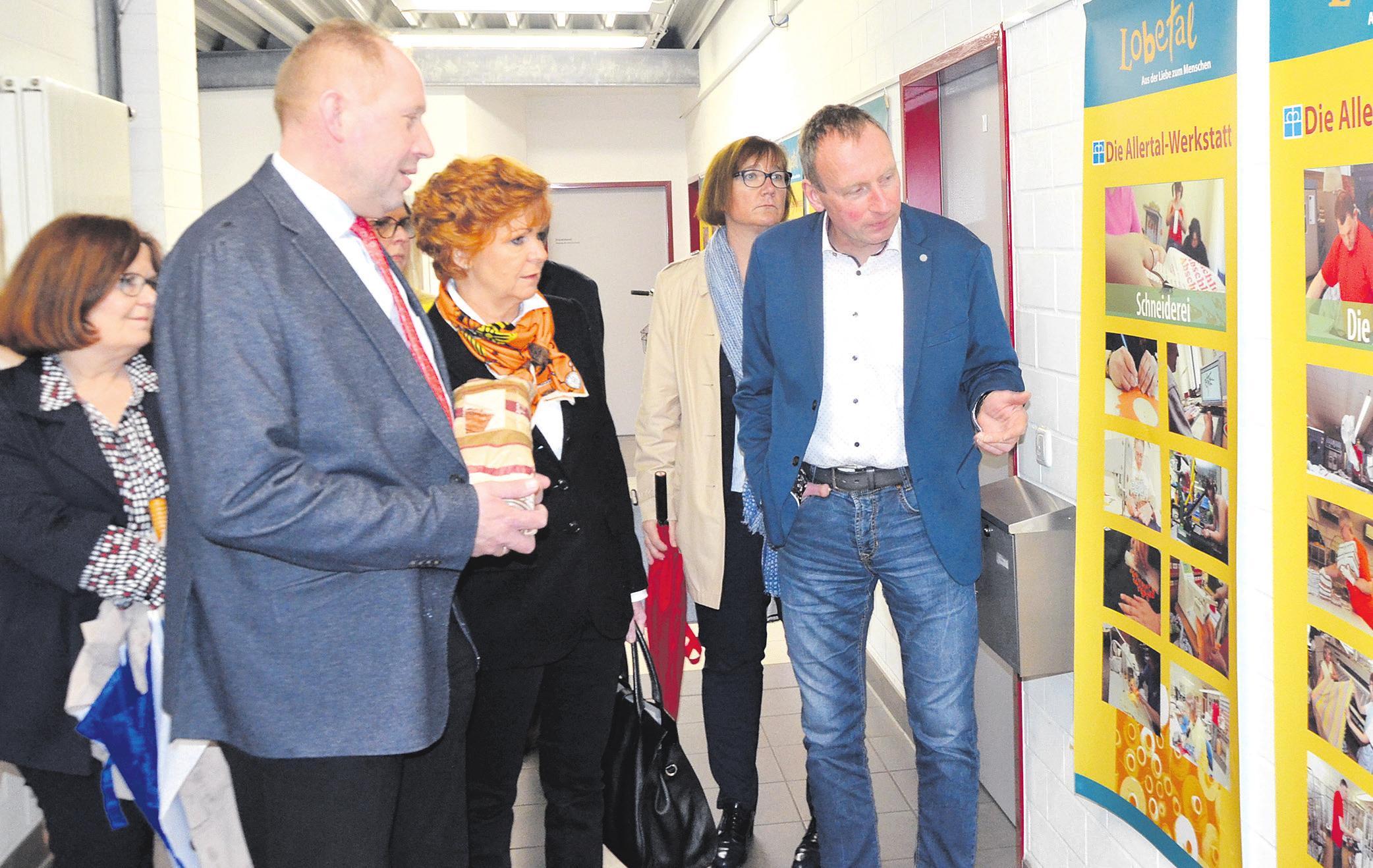 Christine Petersen (von links), Thomas Adasch, Barbara Havliza, Ulrike Drömann und Rainer Nelskamp an den Plakaten im Flur der Allertal-Werkstatt, auf denen die vielen Arbeitsbereiche für Menschen mit Beeinträchtigung aufgezeigt werden. Foto: Wasinski