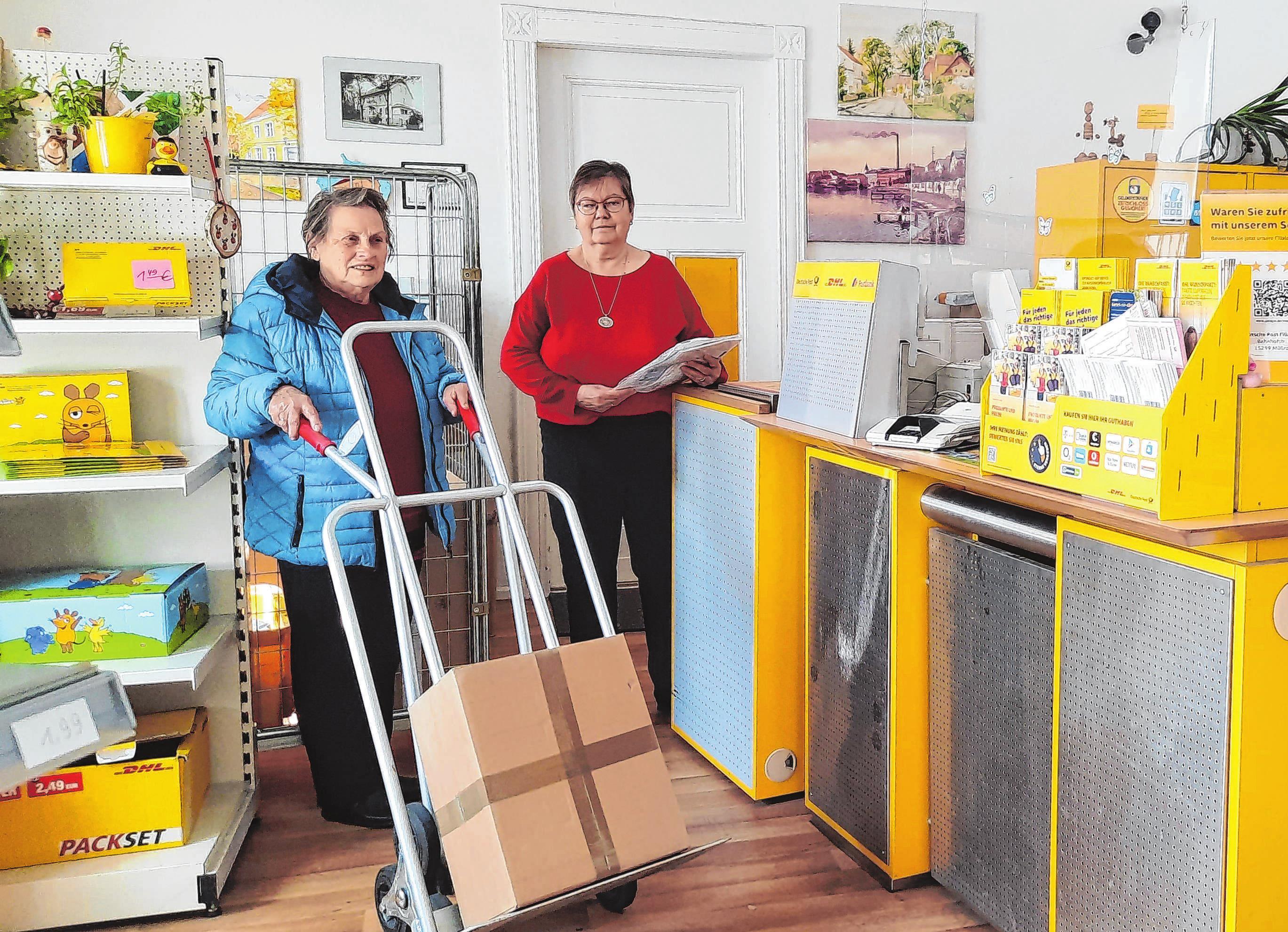 """Für Vera Stange (links), die inzwischen 80 Jahre alt ist, war das Haus in der Bahnhofstraße 5 für 40 Jahre ihr zweites Zuhause. Die Müllroserin arbeitete von hier aus als Postzustellerin; früher sagte man noch """"Briefträgerin"""". Für das Foto schlüpfte Vera Stange noch mal in die Rolle der Postzustellerin, rechts im Bild Adele Reusner."""