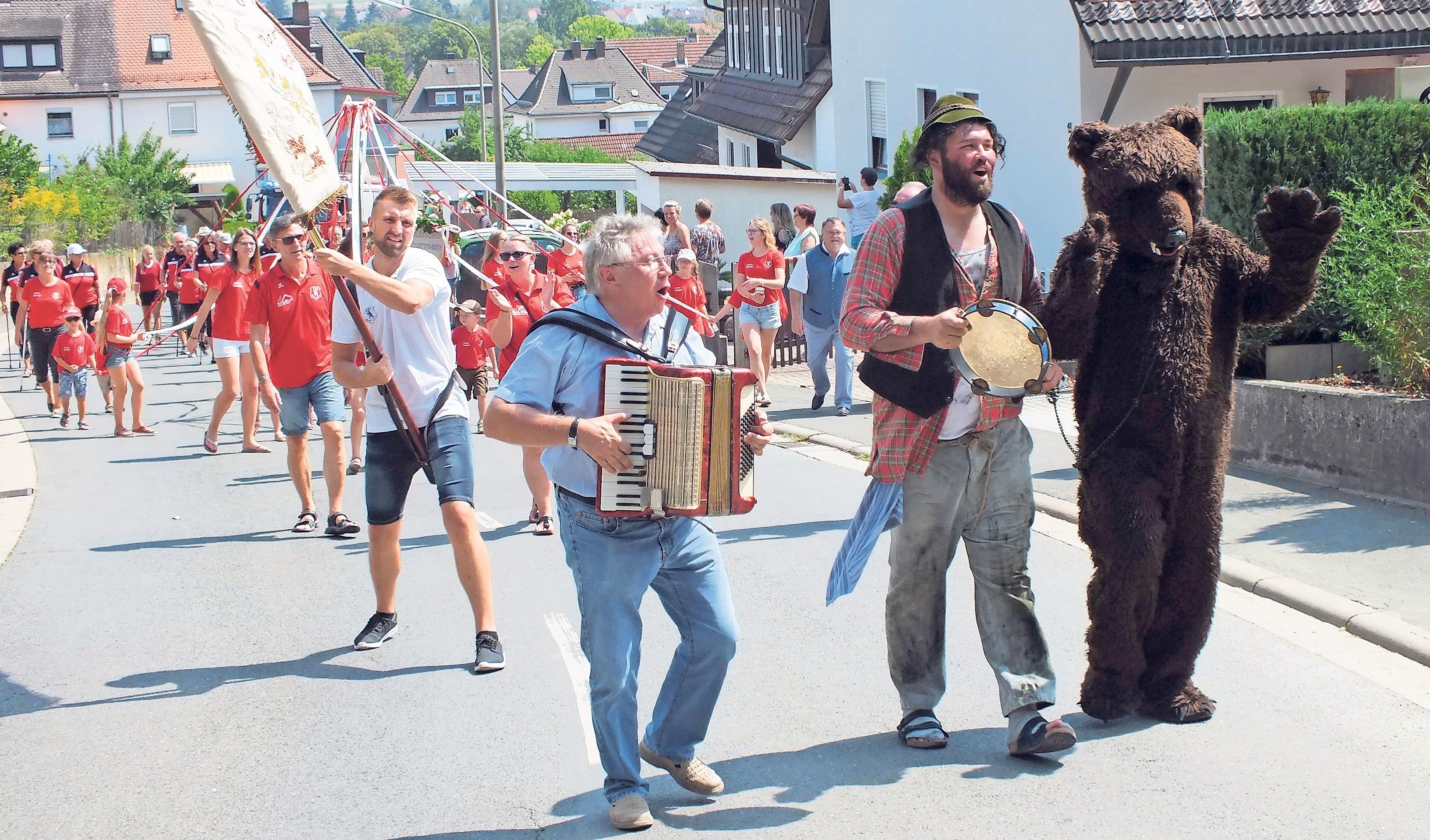 Angeführt von Bär und Treiber, Musiker Ralf Bayerlein und Fahnenträger Dominik Leicht zieht der Festzug am Sonntag durch den Ort zum Sportgelände.
