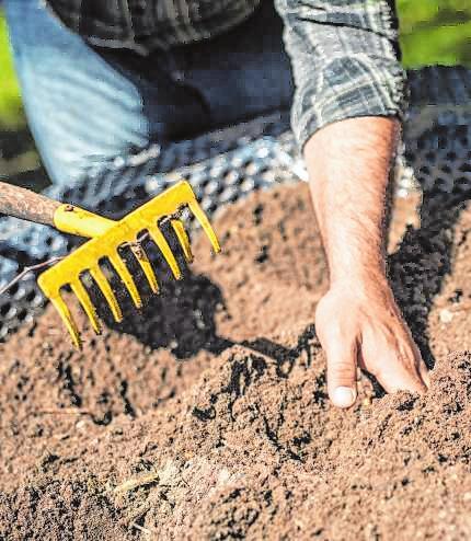 In einem Hochbeet wird die Erde in Pflanzgefäße eingebracht, die durch eine Folie geschützt sind.