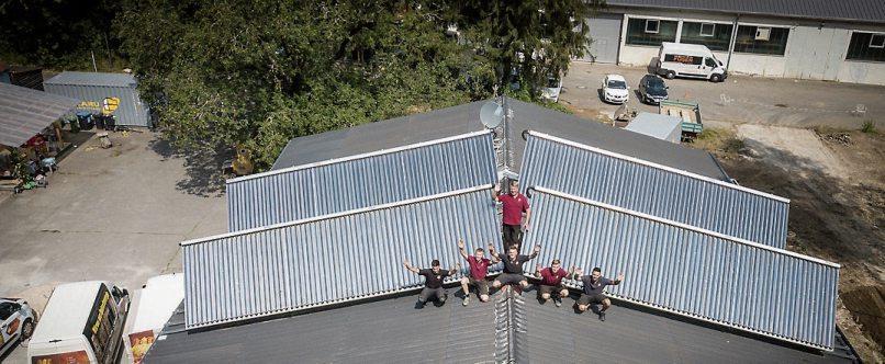 Das Team von Ro-Bi TEC auf einem Solarhaus.