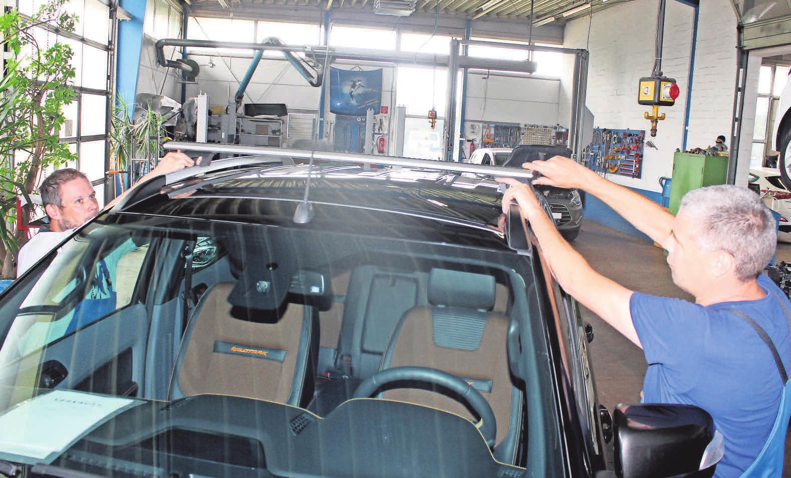 Marco Penack (l.) und Karsten Thiel montieren den Querträger auf das Dach des Fahrzeugs. Auch Dachaufbauten müssen sicher befestigt sein.