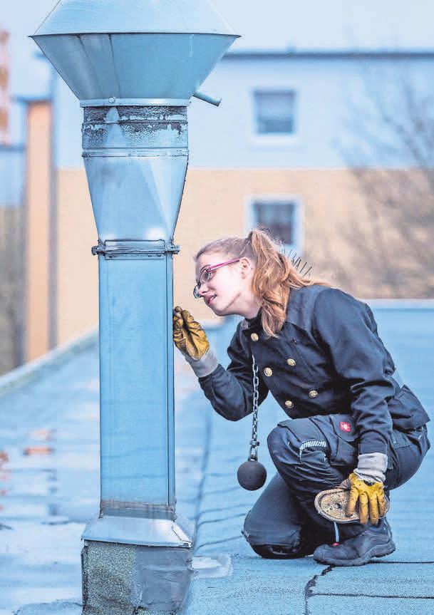 Nichts für Menschen mit Höhenangst: Die Auszubildende Denise Artschwager überprüft auf einem Dach die Mündung einer Dunstabzugshaube auf Fettablagerungen.