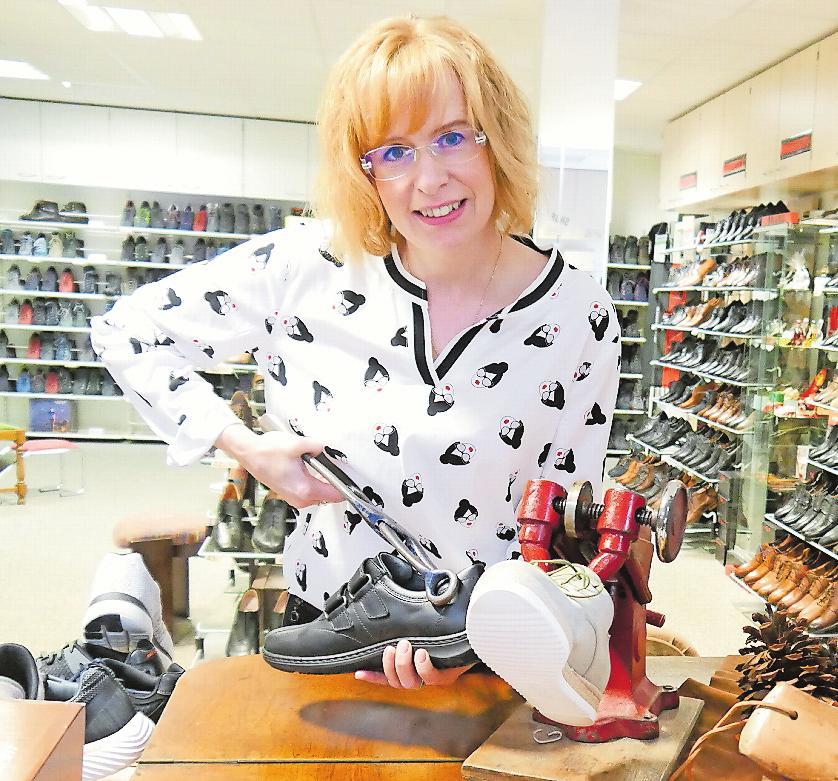 Verkäuferin Marion Adams zeigt, wie sie mit der Schuhzange das Leder weicher macht.FOTO: STEPHANIE BRÄUNLING