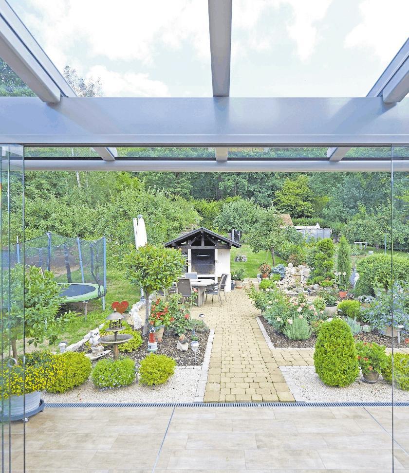 Die leichtgängigen Ganzglas-Schiebetüren können mit wenigen Handgriffen geschlossen oder geöffnet werden. Im geschlossenen Zustand beeinträchtigen die rahmenlosen Glaselemente den Blick in den Garten in gar keiner Weise. FOTO: DJD/SONNE-AM-HAUS.DE