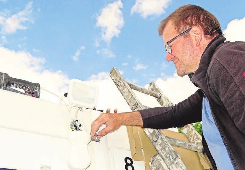 Der langjährig erfahrene Mitarbeiter Harald Bieschke bei der Installation von Bewegungsmeldern.