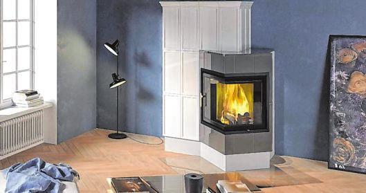 Markantes Farbenspiel im Stil des Raumes: Die Ofenkeramik unterstreicht die Wirkung der Holzfeuerstätte.