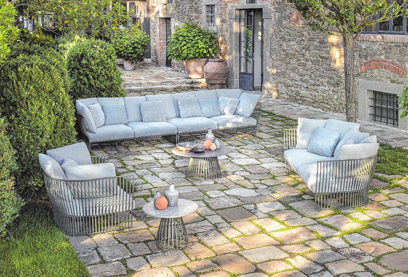Outdoormöbel haben aktuell häufig ein reduziertes, schlichtes Design. Die Sofas und Beistelltische von Ethimo zum Beispiel wirken schlanker durch eine Lehne aus dünnen Stäben.