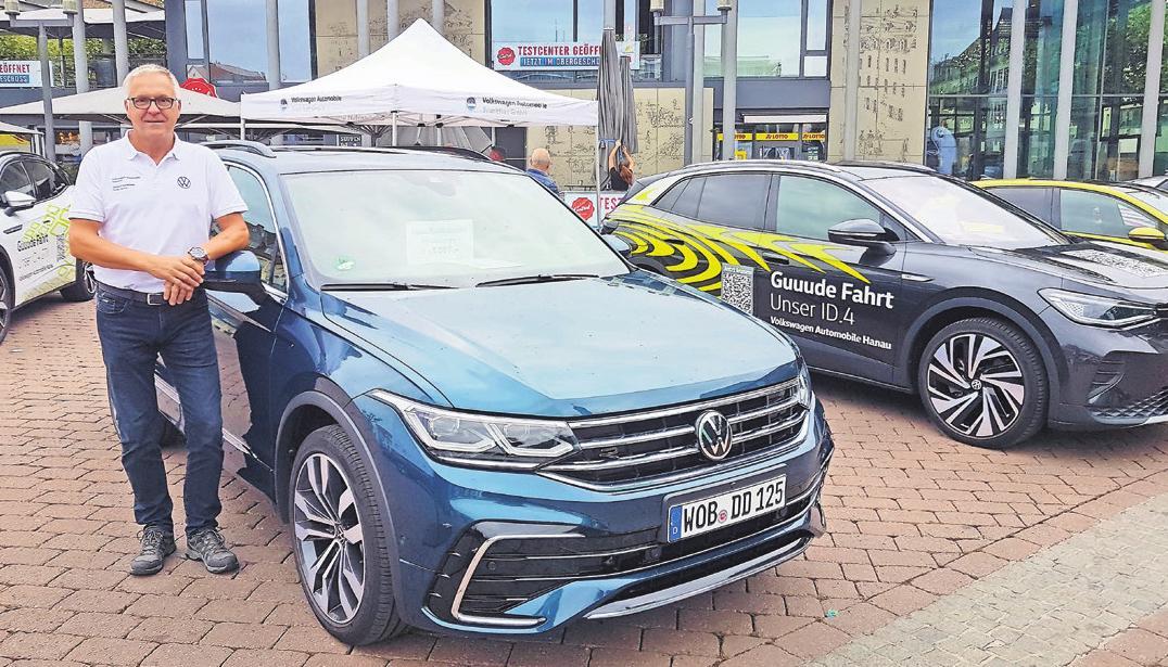 Verkaufsleiter Frank Seume mit VW Tiguan E-Line E-Hybrid am Stand des Autohauses Volkswagen Automobile Hanau.