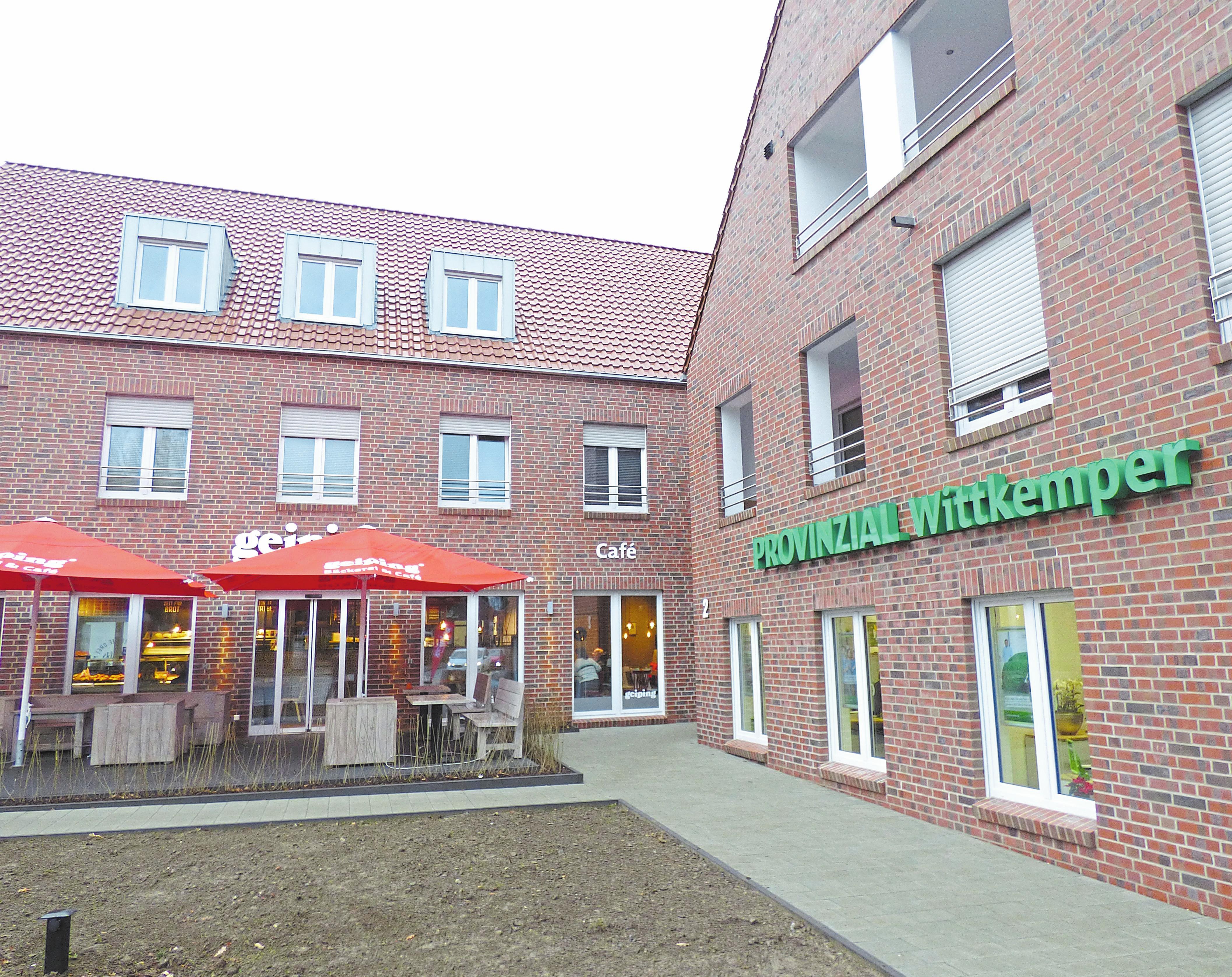 Von der Hauptstraße aus blickt man in Richtung Café-Terrasse. Direkt daneben die Filiale der Provinzial. Zwischen Café und Versicherung befindet sich der Eingang für die Mietparteien.