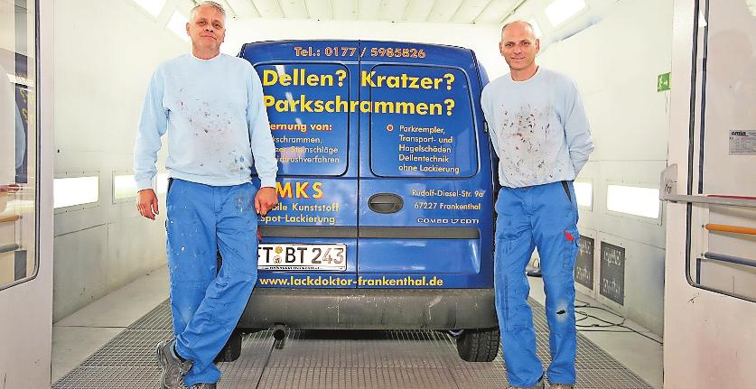 """Thomas Baumgärtner (links) und Mitarbeiter Patric Ginkel – hier vor der Lackierkabine –""""heilen"""" das """"heilig Blechle"""". FOTO: WIP"""
