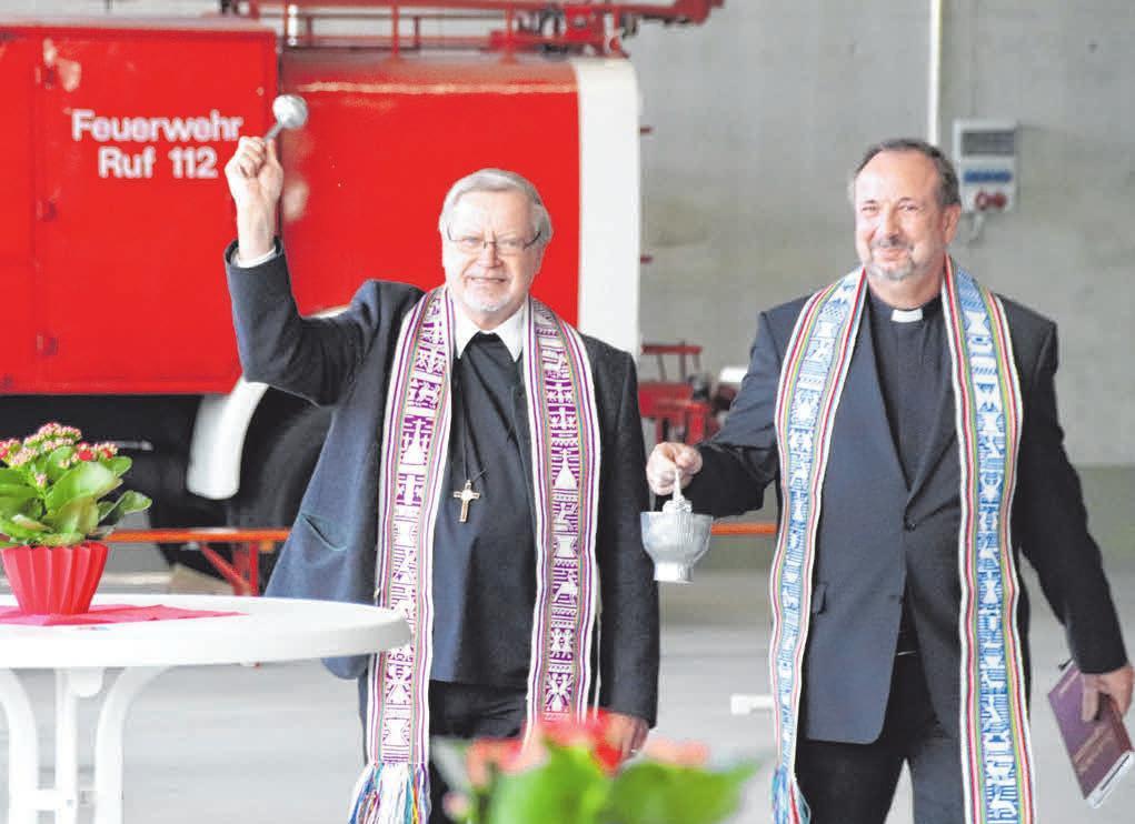 Dekan Sigmund Schänzle von der Katholischen und Pfarrer Jörg Schwarz von der Evangelischen Kirchengemeinde segnen das neue Feuerwehrhaus. FOTO: MARKUS FALK