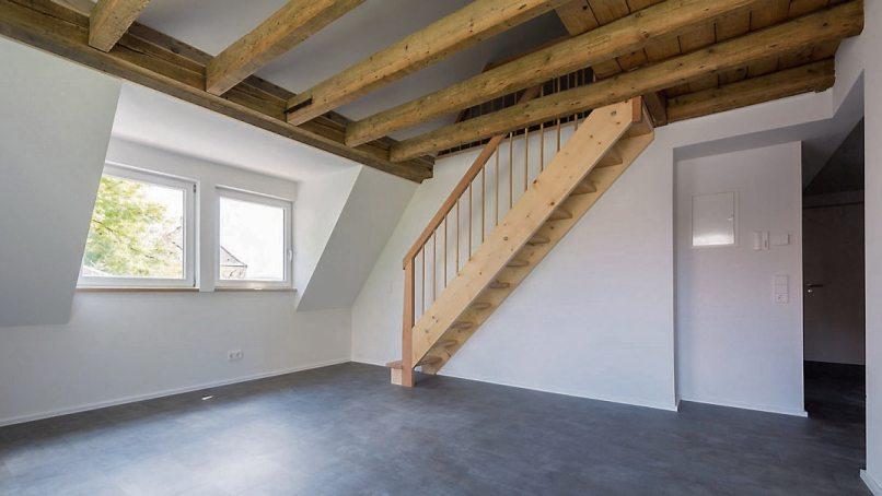 Bild links: Die Wohnung im Dachgeschoss des Gebäudes mit den alten, aufbereiteten Holzbalken.