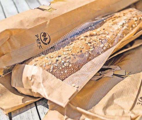 Den Einkauf für die Frühstückspause packt der Bäcker in eine Brötchentüte mit dem Siegel.