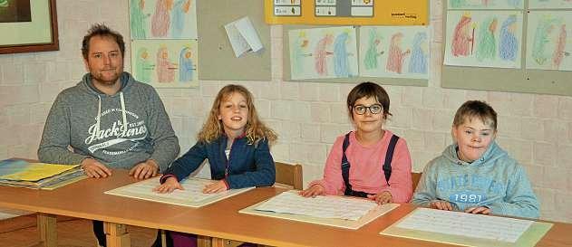 Die dritte Klasse behandelt aktuell den Schöpfungsbericht. Heilpädagoge Christopher Winkelmann und seine Schüler Emilia (9), Amelie (10) und Mika (9) sind stolz auf ihre zum Thema passenden Schreibübungen (v.li.n.re.). FOTO: REG