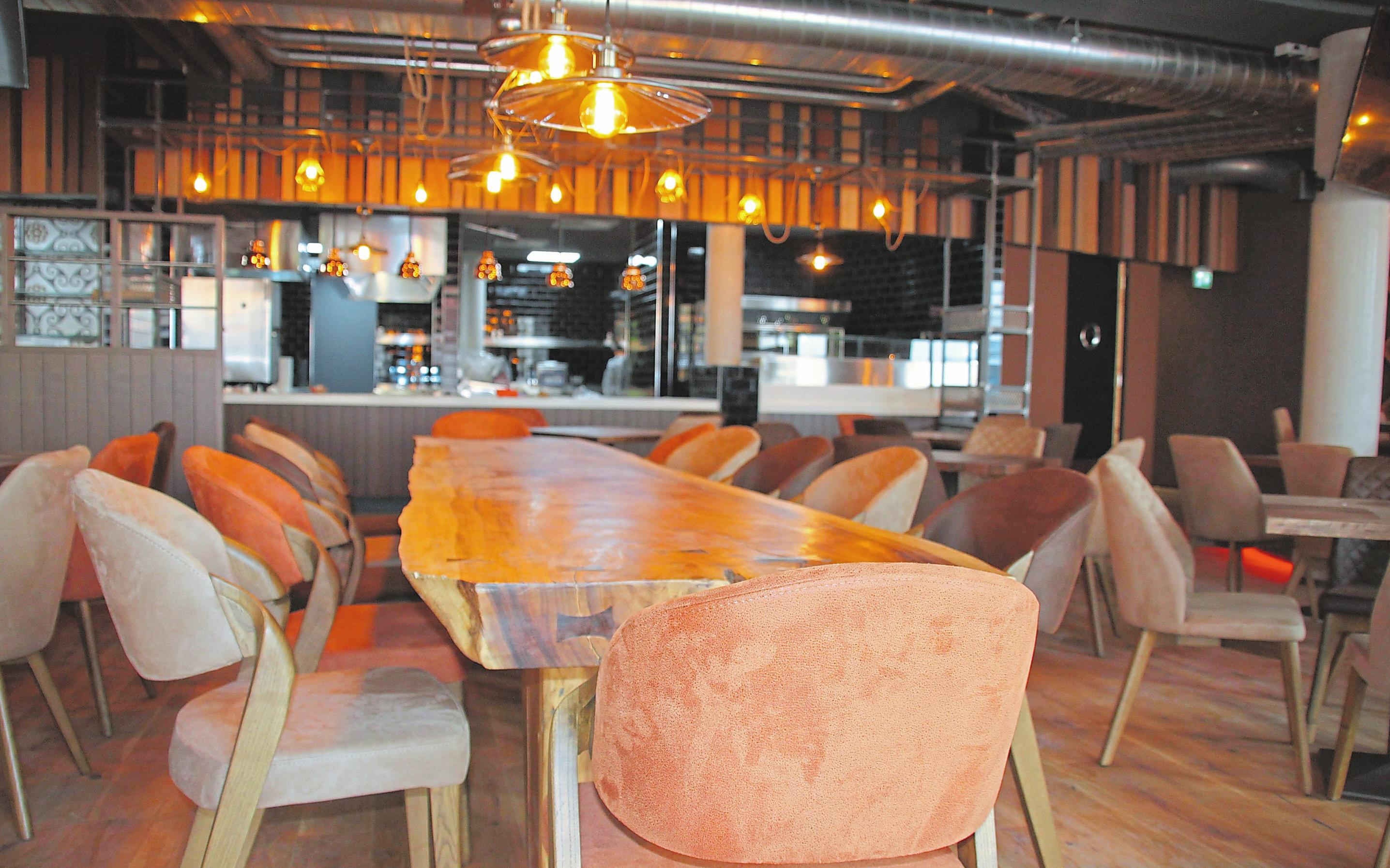Massive Holztische, hochwertige Stühle und die offene Show-Küche im Hintergrund, so präsentiert sich das Mezzomar.Foto: Jan-Philipp Jenke