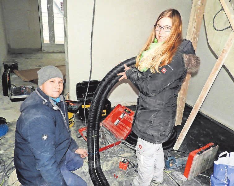 Die Auszubildenden Sina Meiberth und Dennis Brieske verlegen ein Flexrohr für Zuleitungen.