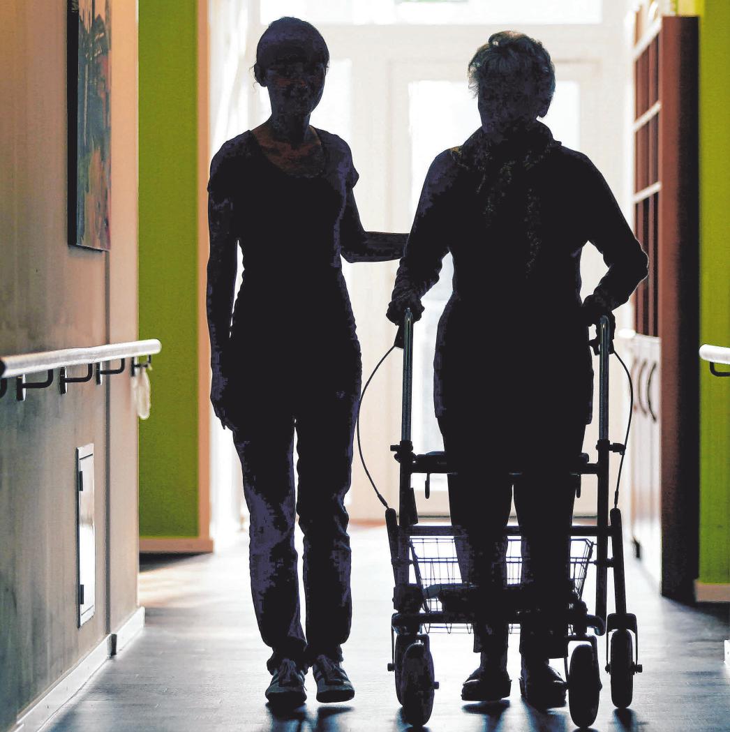 Eine Pflegekraft (l) begleitet die Bewohnerin eines Altenheims im den Flur. FOTO: BERG