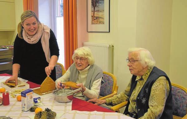 Thekla Lunow (li.) bastelt gemeinsam mit den Bewohnerinnen Ursula Groth und Irmgard Kraupner leckere Knusperhäuschen für die Adventszeit. FOTO: ULRIKE VOLKMANN