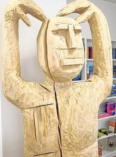 Hingucker: Im Inneren des Buchladens begrüßt eine große Holzfigur die Kunden.