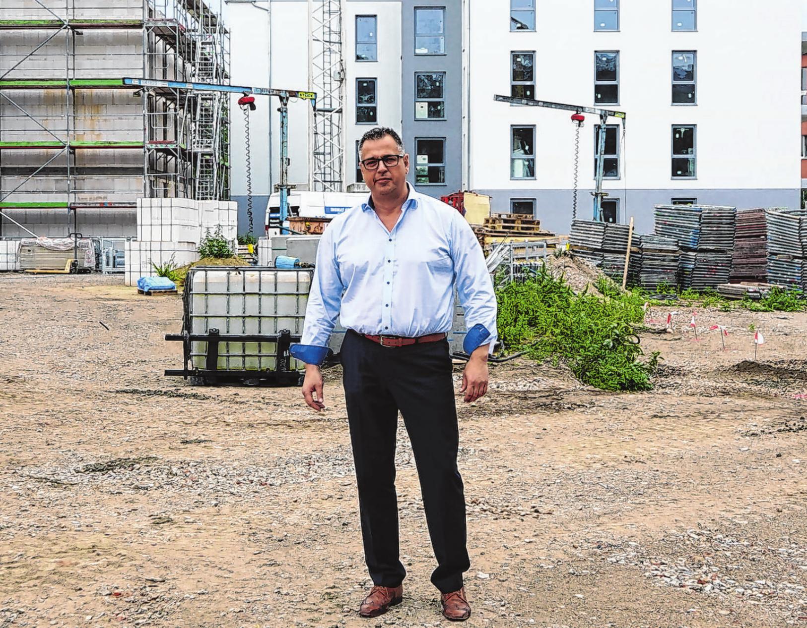 """Dirk Schulze, einer der Geschäftsführer der Unternehmensgruppe Krebs & Schulze, vor dem Wohnquartier """"An der Marina"""". Das erste Gebäude ist fast fertiggestellt, das zweite befindet sich im Bau. Fotos (2): Andrea Steinert"""
